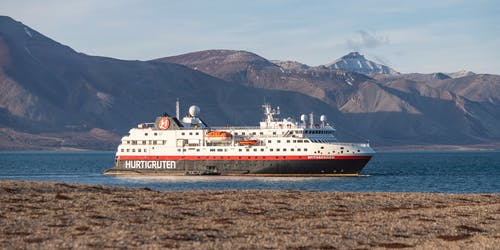 Bild från Svalbard på Hurtigrutens fartyg som kryssar fram mellan bergen.