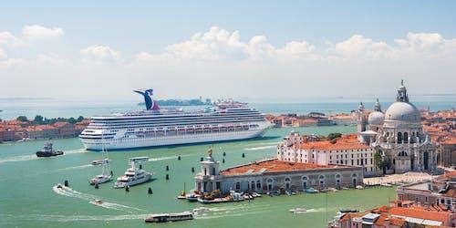 Carnival Freedom kryssar fram mellan färgglada byggnader i Medelhavet.