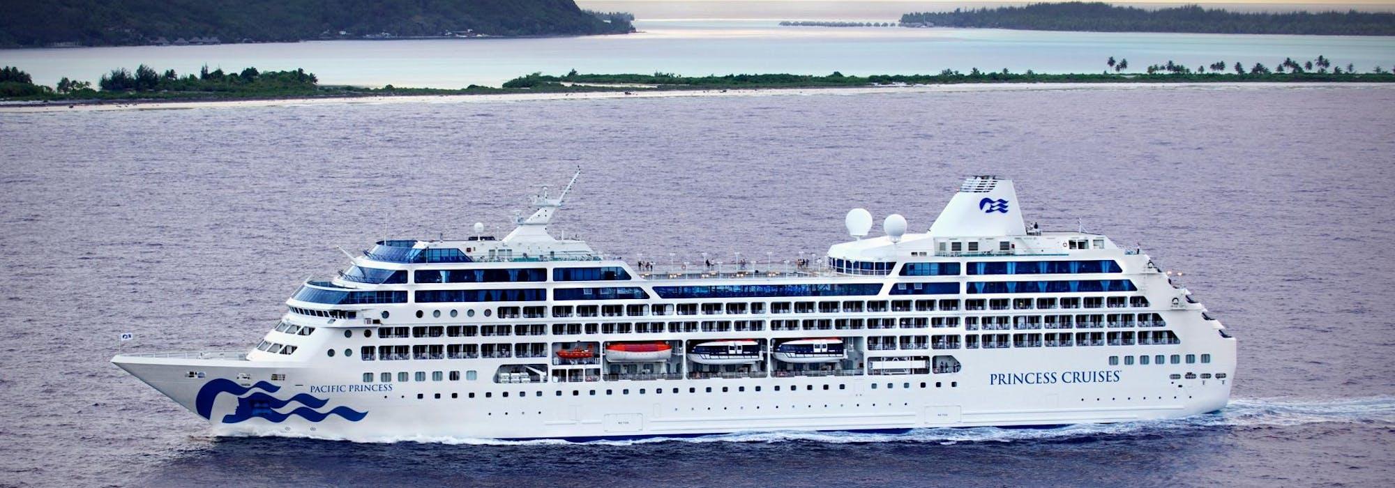 Bild från sidan på Pacific Princess kryssandes framåt med en mindre ögrupp i bakgrunden.