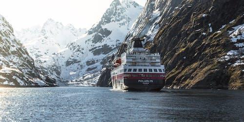 Bild på fartyget MS Polarlys akter medan fartyget lider fram mellan snötäckta berg i de norsk fjordarna.