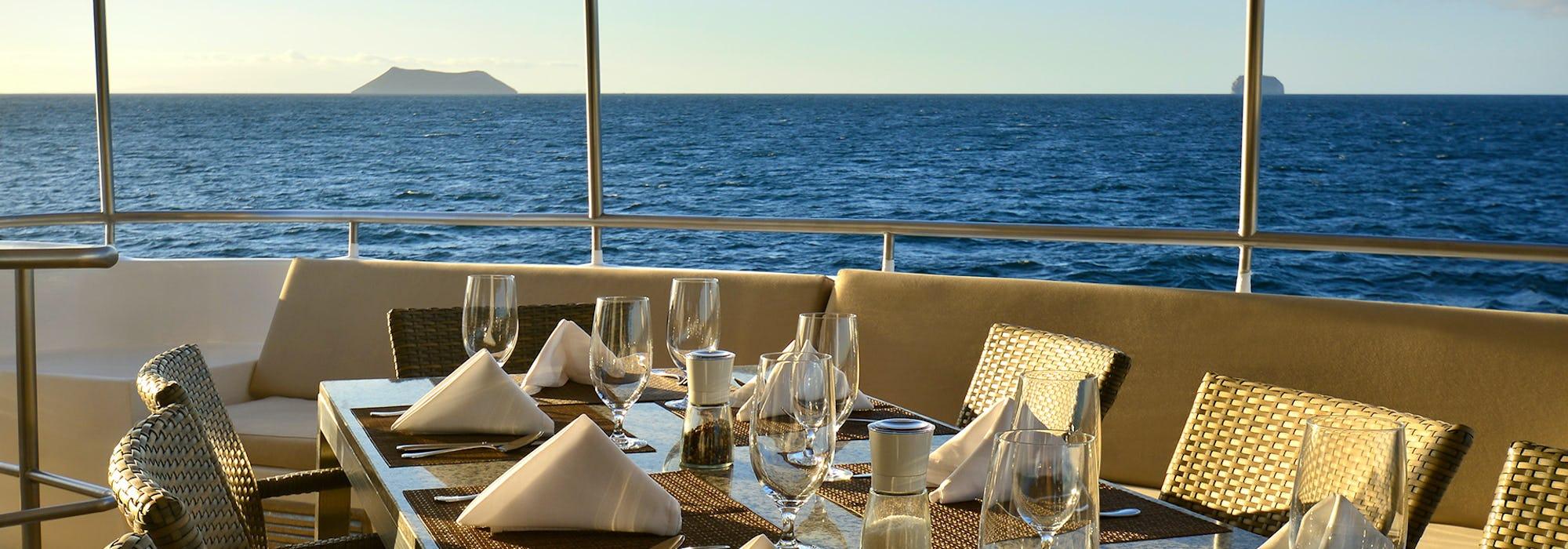 Bild på ett fint dukat bord ombord på Celebrity Xploration med det blåa havet i bakgrunden.