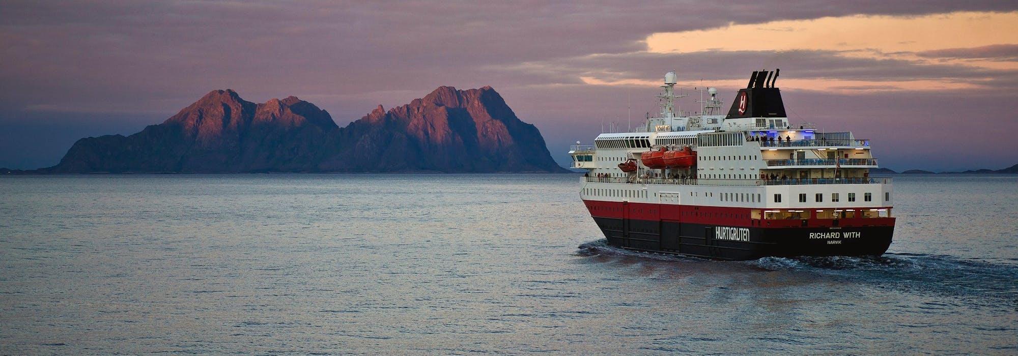 Bild på fartyget MS Richard With i solnedgången med ett berg i bakgrunden.