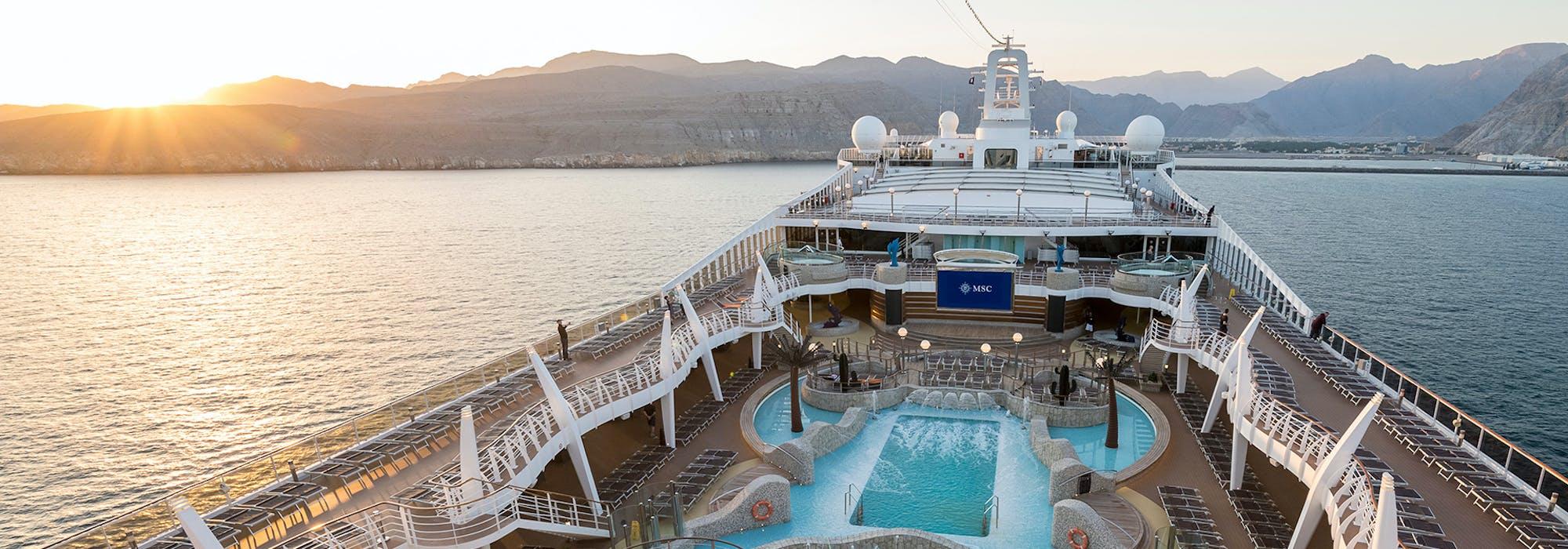 Vacker bild på MSC Splendidas sol- och pooldäck när fartyget närmar sig en hamn i solnedgången.