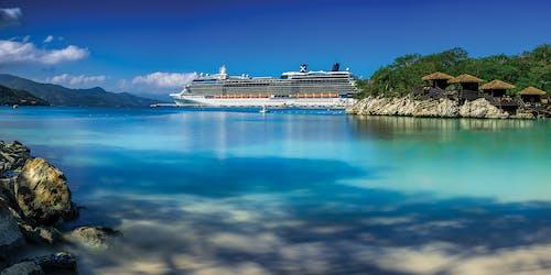 Celebrity Silhouette uppenbarar sig i bakgrunden med ljusblått vatten och en tropisk ö i förgrunden.