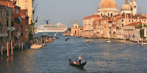 Fartyget Carnival Liberty kryssar fram utanför Venedig. På bilden syns vackra byggnader och gondoler.