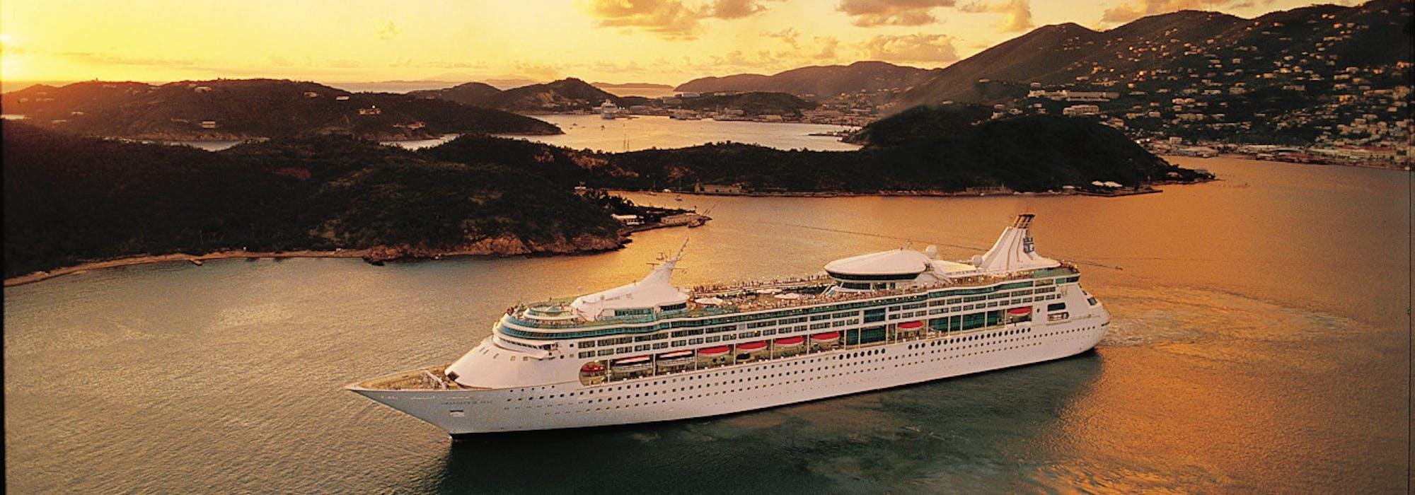 Bild på Rhapsody of the Seas, taget från sidan, utanför en Karibisk ö i solnedgången.