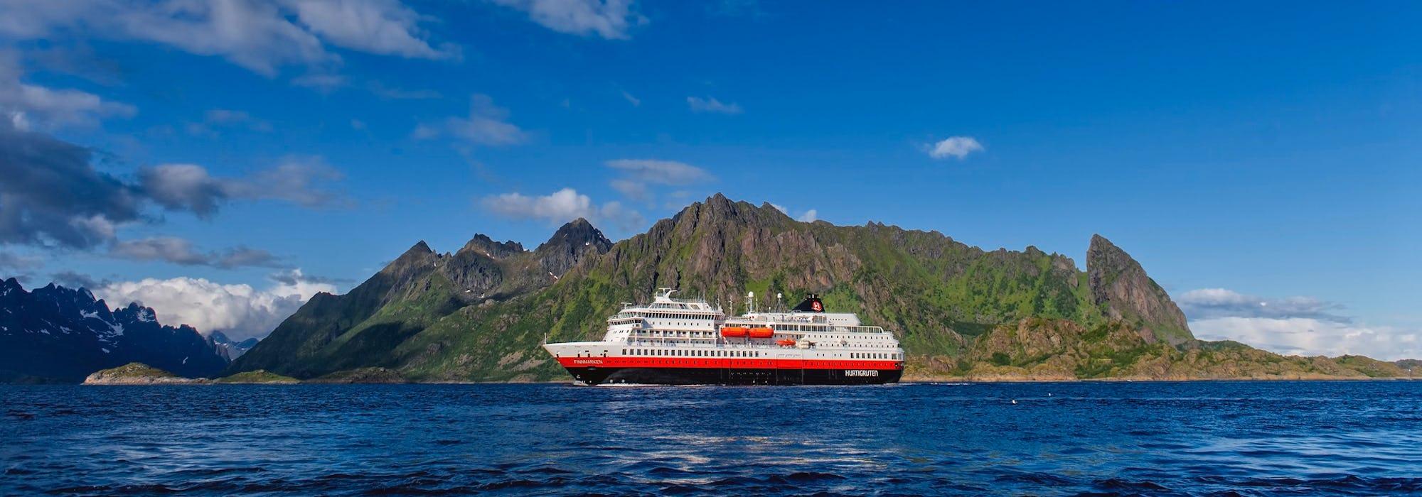 Bild tagen från sidan på fartyget MS Otto Sverdrup som kryssar fram framför ett grönt berg.