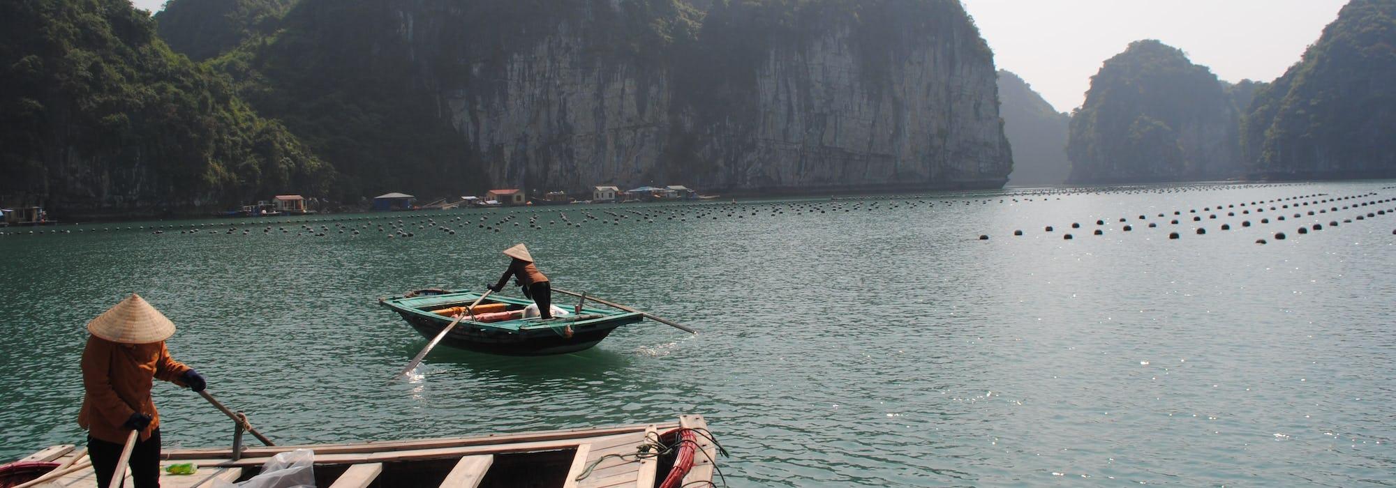 Två människor i båtar paddlar fram framför vackra berg.