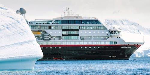 Fartyget MS Midnatsol glider fram framför ett större isberg i Antarktis.