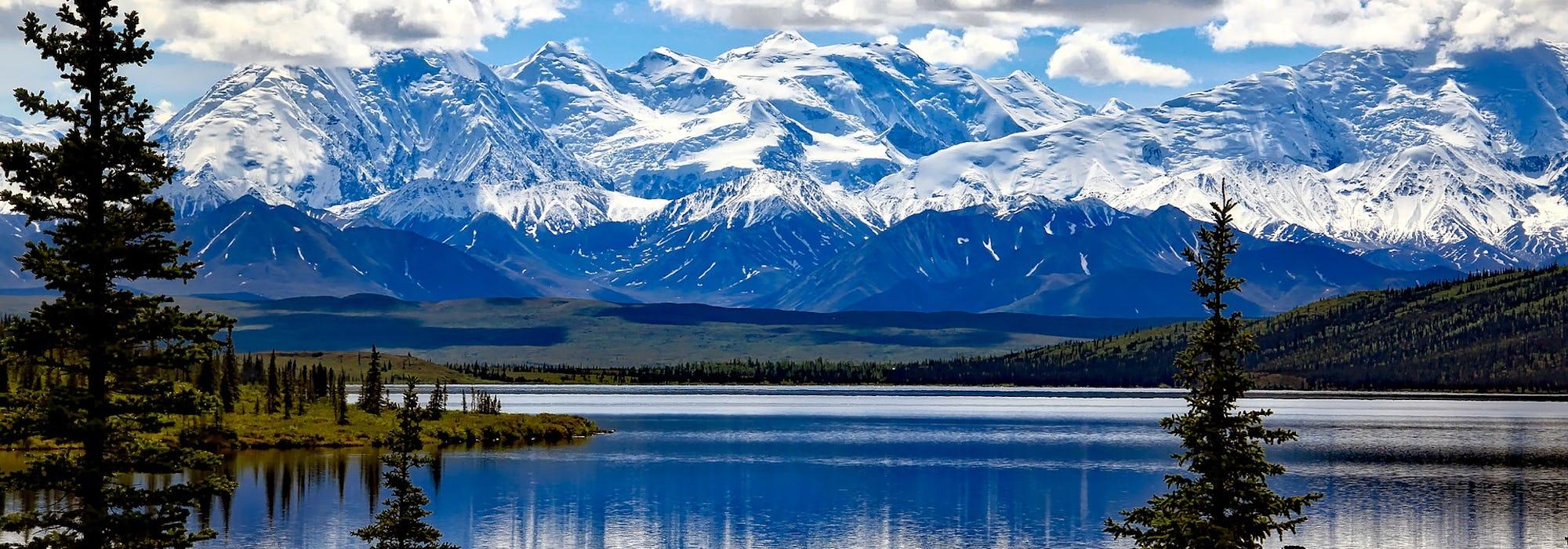 Alaskas oslagbara natur med skog, snötäckta berg och stilla vatten.
