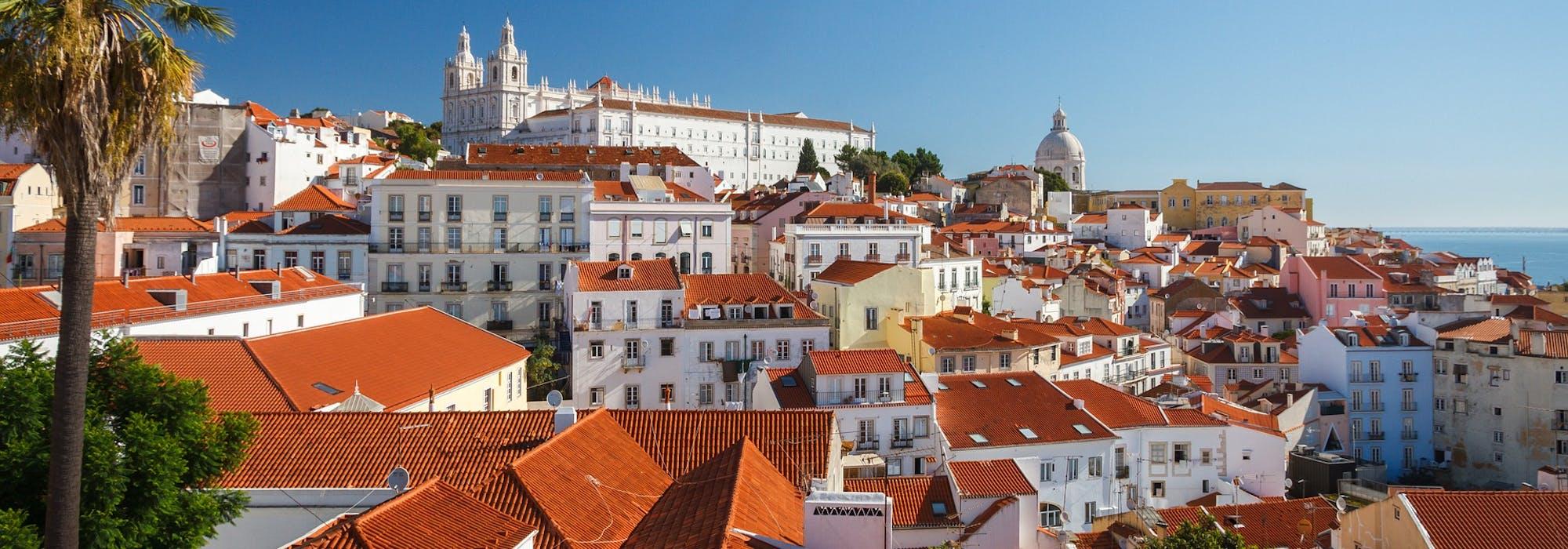 Bild från ovan på färgglada hus i Lissabon med havet i bakgrunden.