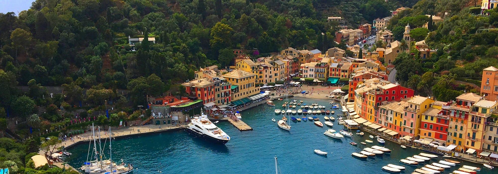 Portofinos hamn med båtar, gröna träd och färgglada hus.