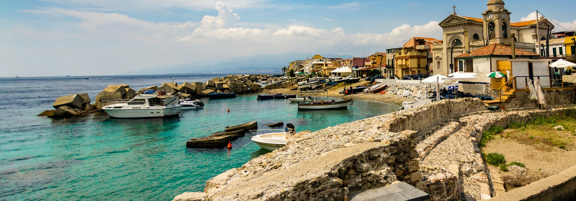 Messina i Italien med havet, små båtar och gamla byggnader.
