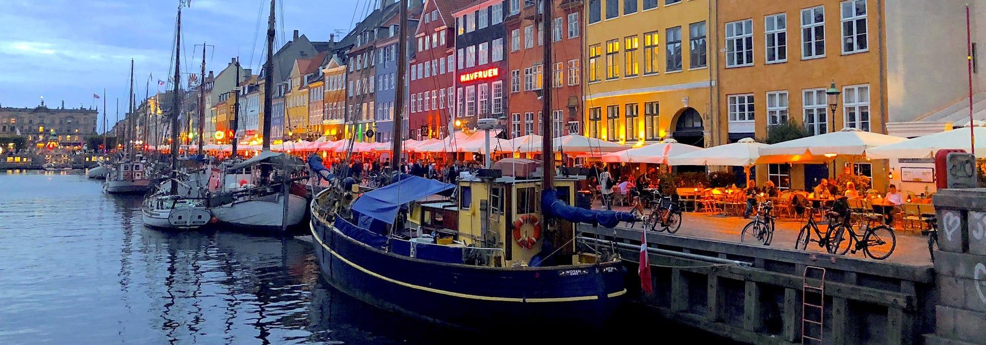 Bild på skepp som ligger vid hamn med färglada hus i bakgrunden.