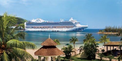 Fartyget Crown Princess ligger ankrad utanför en hamn i exotiska Jamaica. I framkant syns palmer och vit sand.