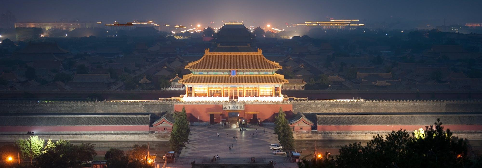 Bild på den förbjudna staden i Peking tagen uppifrån med det ståtliga palatset upplyst i kvällsljuset.