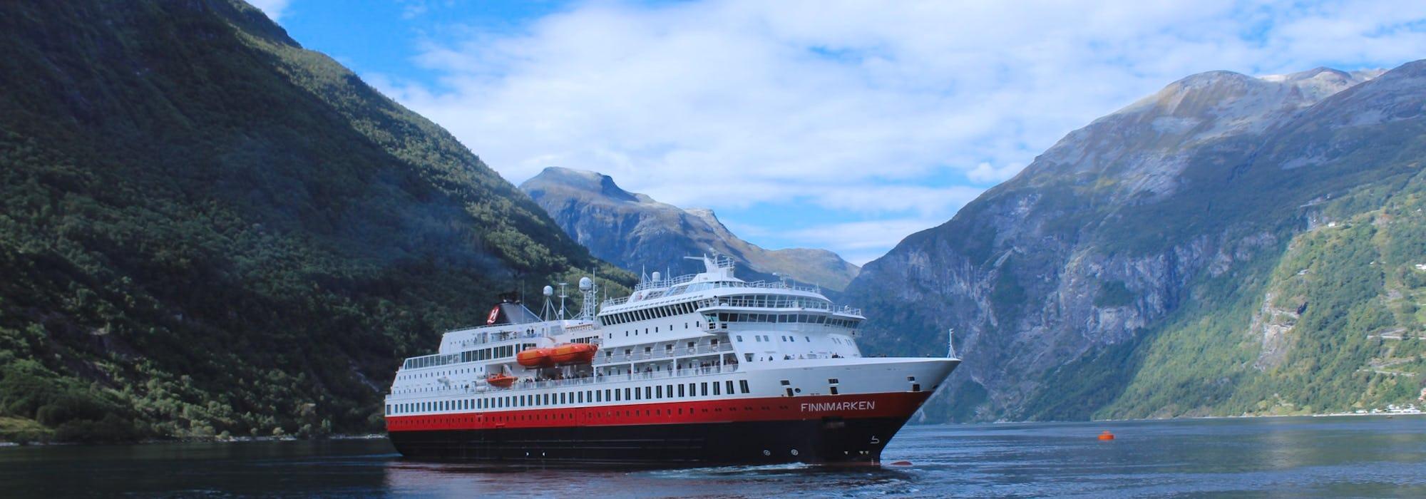 Fotografi på fartyget MS Finnmarken, taget från sidan medan det glider fram i vattnet mellan de höga bergen.