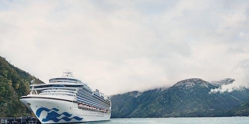 Fartyget Ruby Princess i framkant och höga berg med moln som omringar dem i bakgrunden.