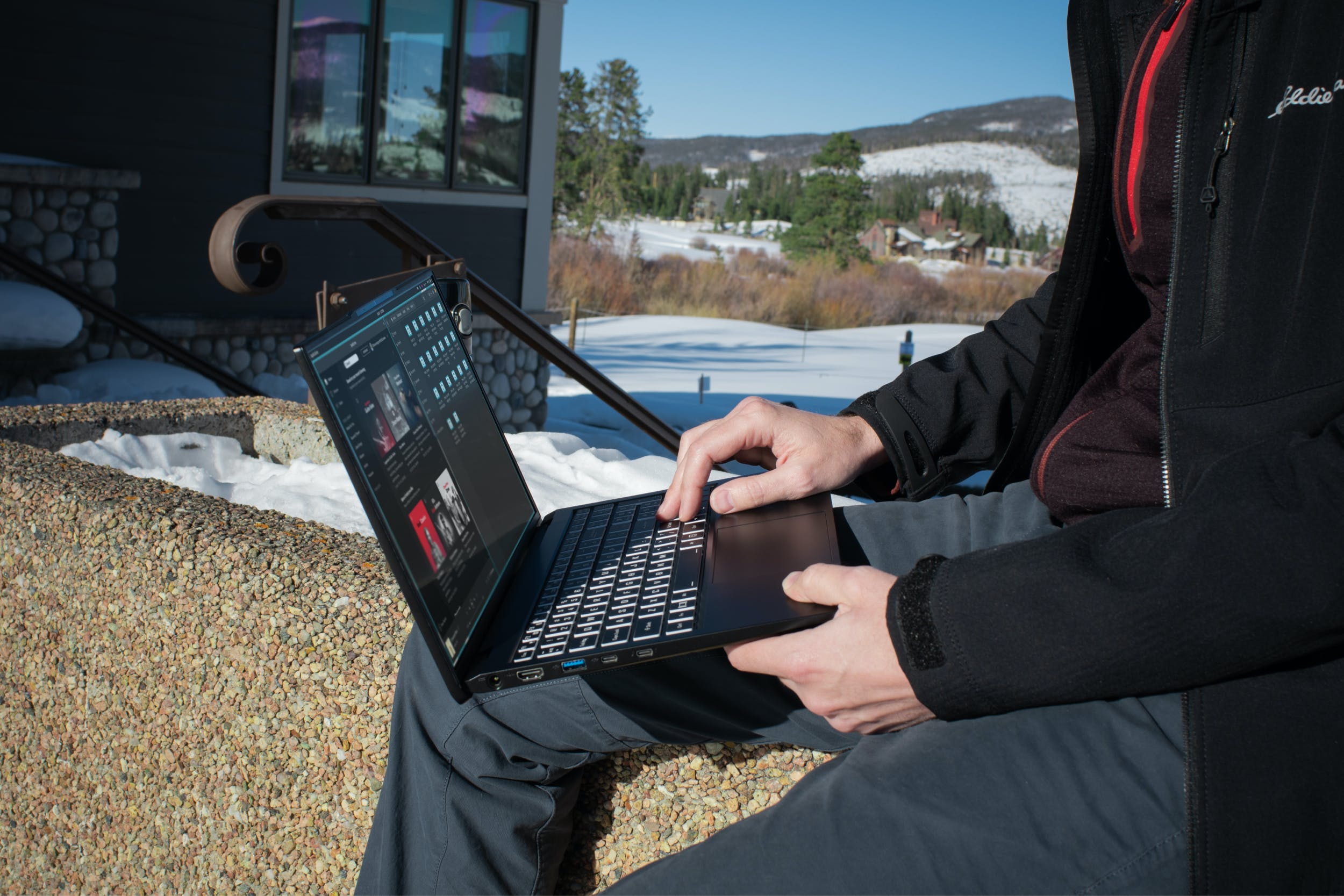 A person using the Darter Pro laptop in a snowy park.