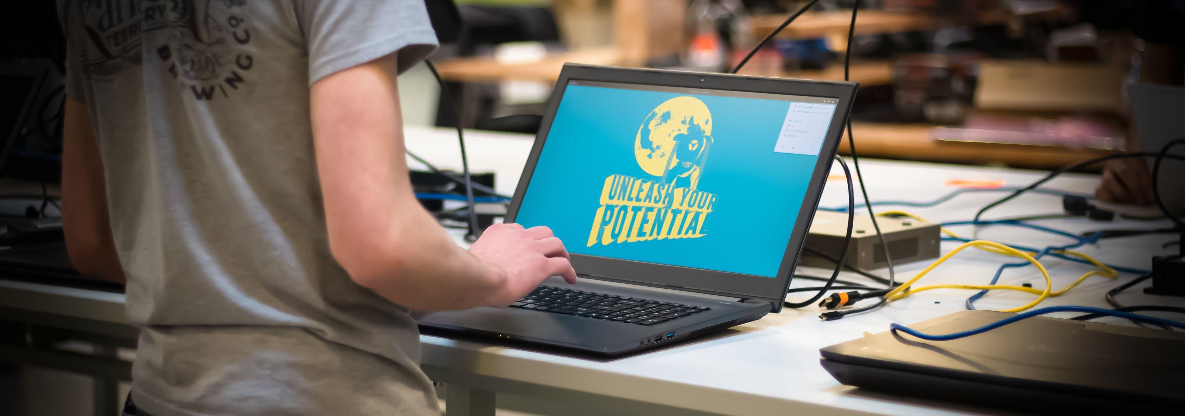A developer programming on a System76 laptop running Pop!_OS