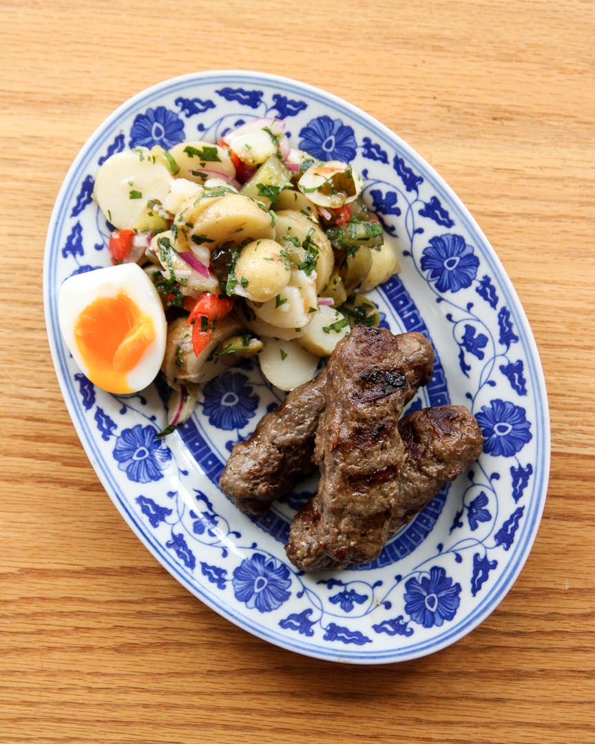 Mititei beef sausages with Romanian potato salad and soft-boiled egg