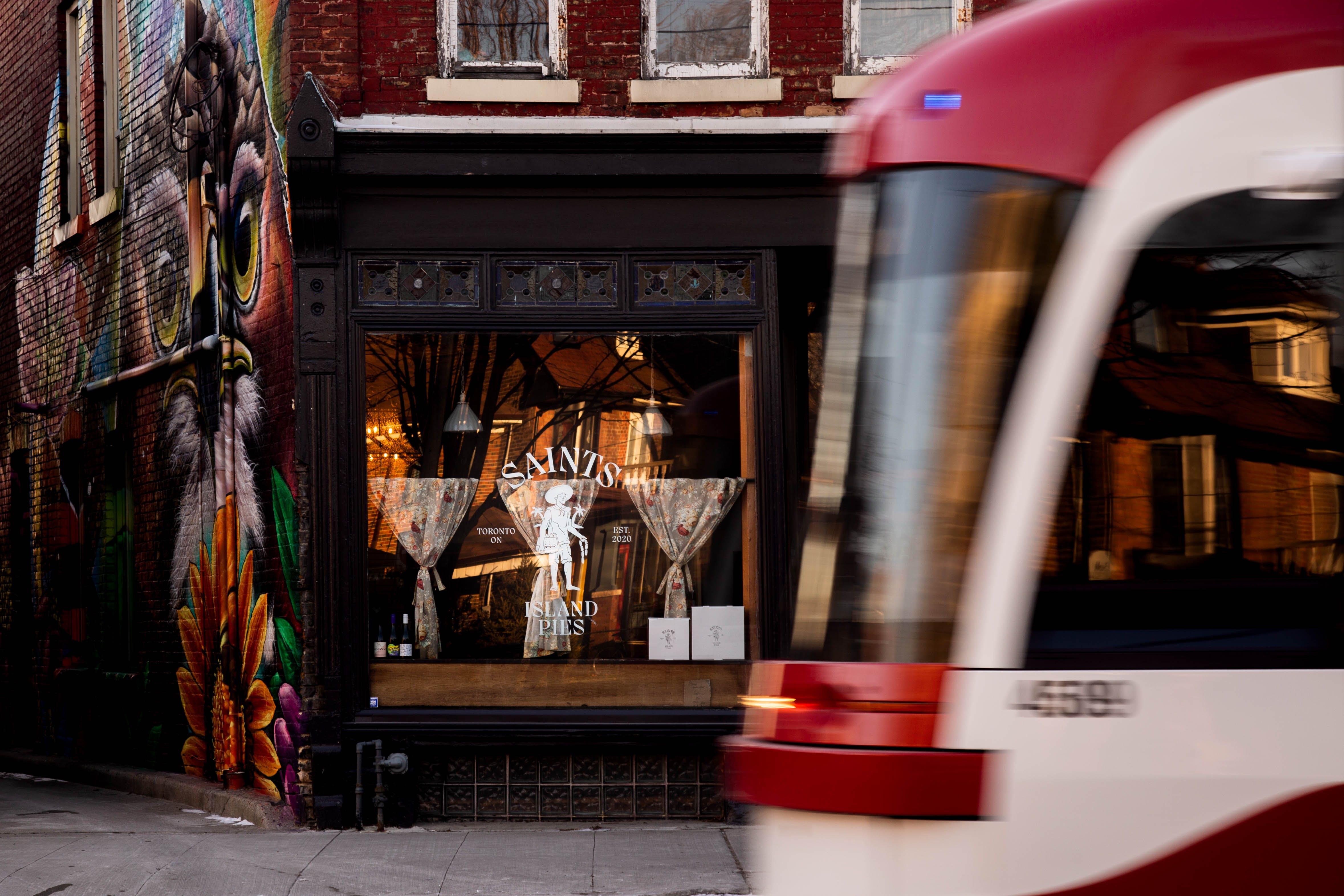 A TTC streetcar passes by Saints Island Pies restaurant on Dundas Street West in Toronto.