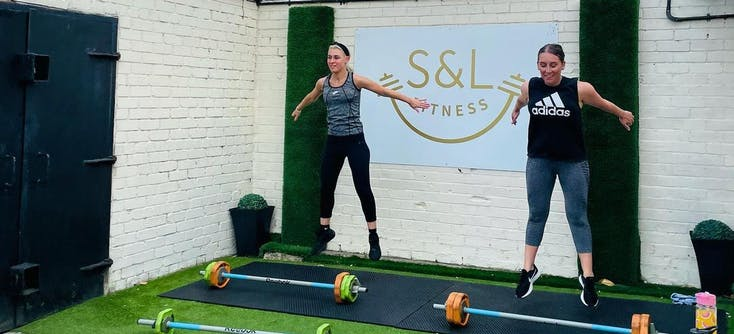 Two participants taking part in an outdoor workout session