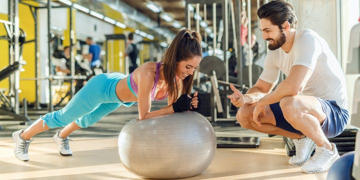 3 personal trainer and customer working out at the gym