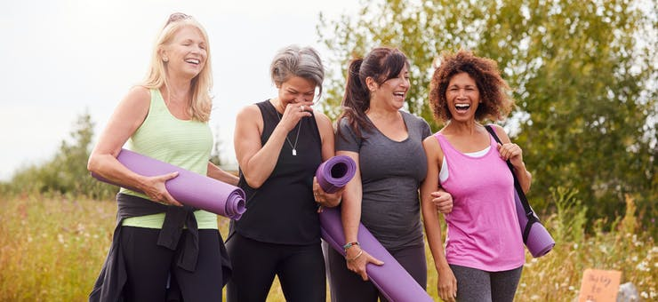 Women holding yoga mats and laughing.