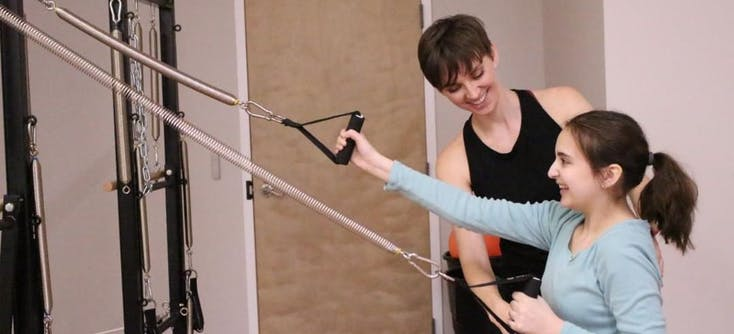 An instructor helping someone learn to teach Pilates in a Pilates studio