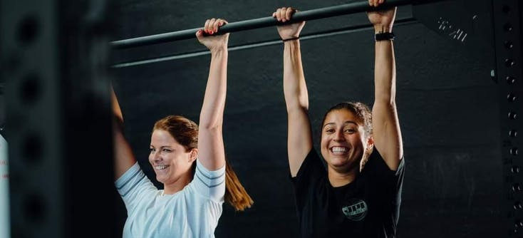 two girls at the gym holding onto a bar