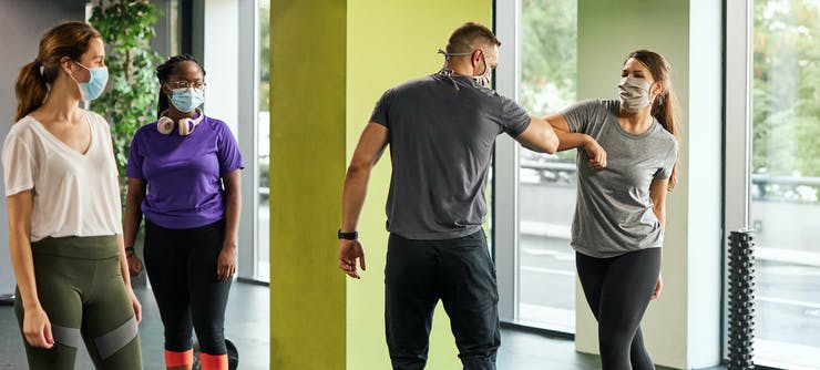 fitness instructor welcoming customers back to class