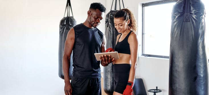 gym owner showing a customer how to use their tablet