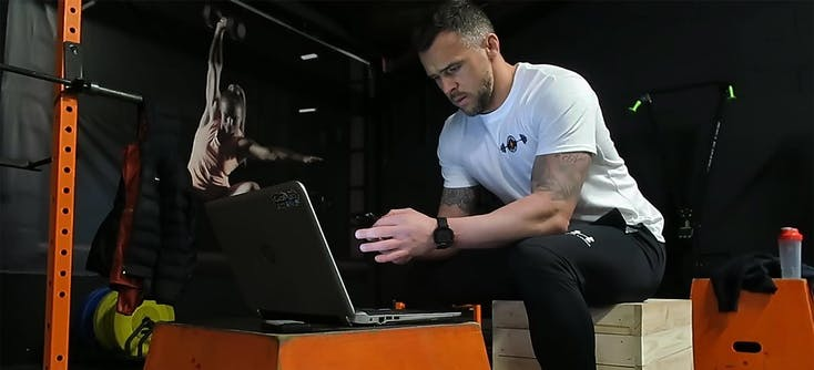 A personal trainer checking his social media on his phone and laptop in his fitness studio.