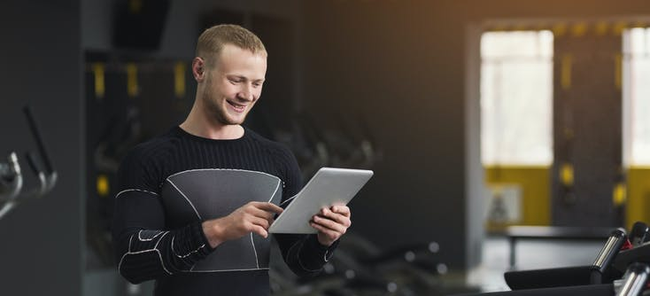 gym owner checking his reports on his tablet