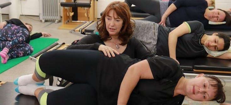 karen grinter helping a pilates student during a pilates class