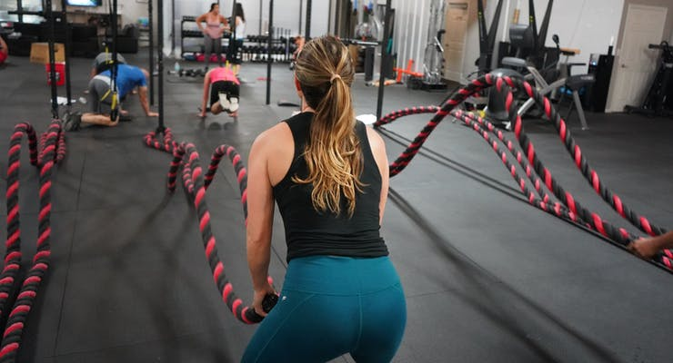 girl at the gym working out with ropes