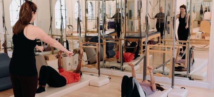 An instructor leading a Pilates class in their Pilates studio