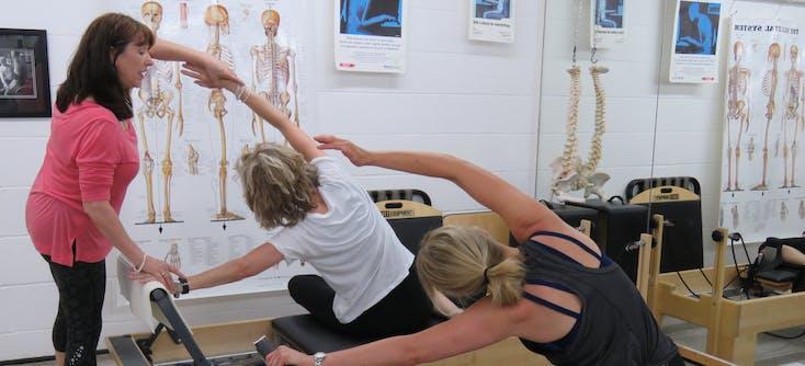 karen helping a pilates student during class
