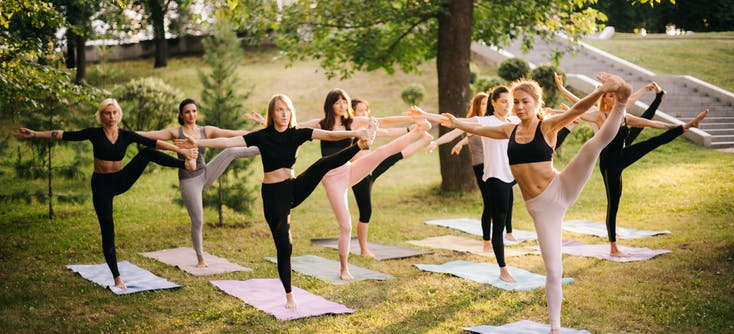 group of women doing pilates in the park