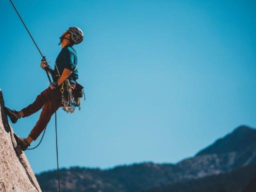 A man climbing a vertical rock face in Catalonia