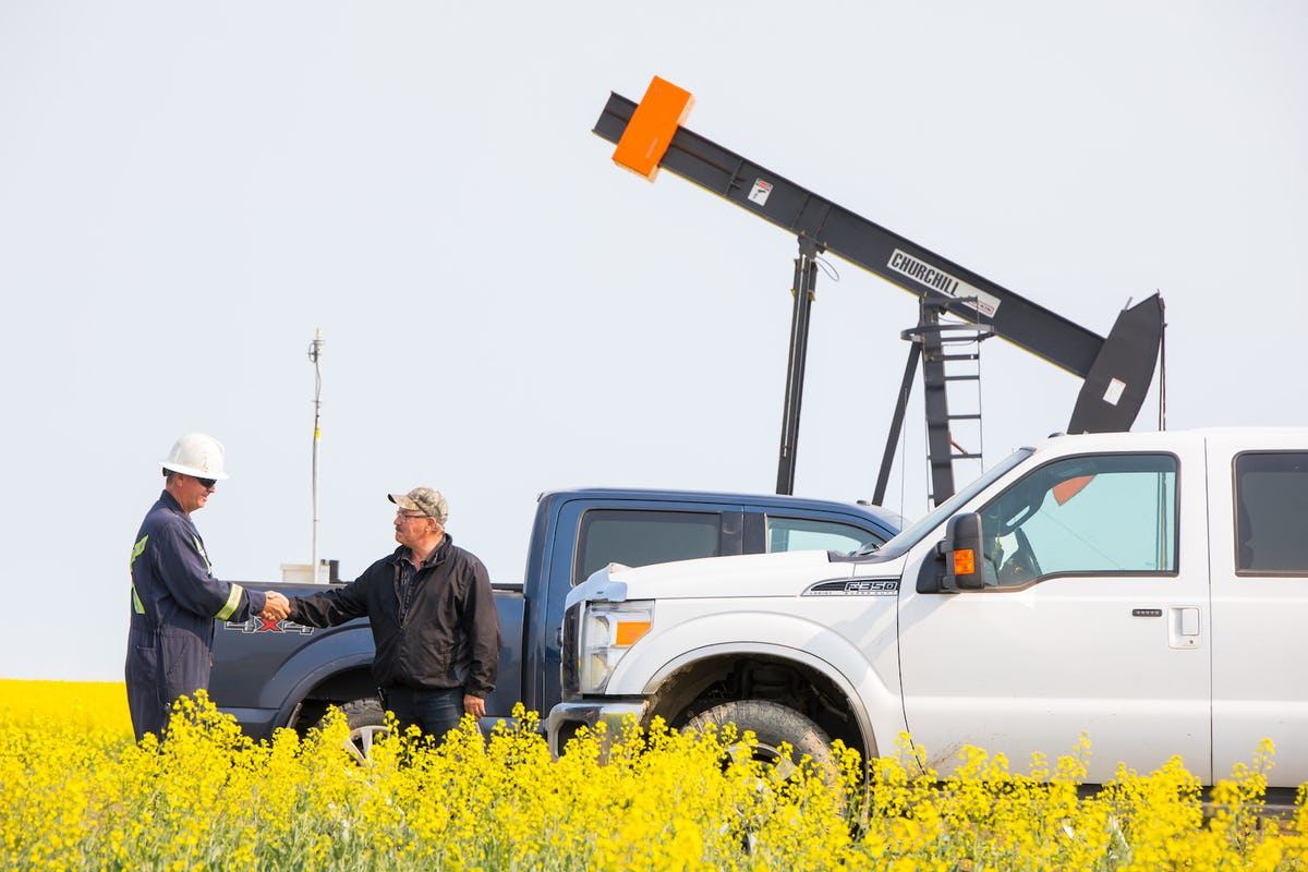 Two men shaking hands in a canola field, in front of oil machinery.