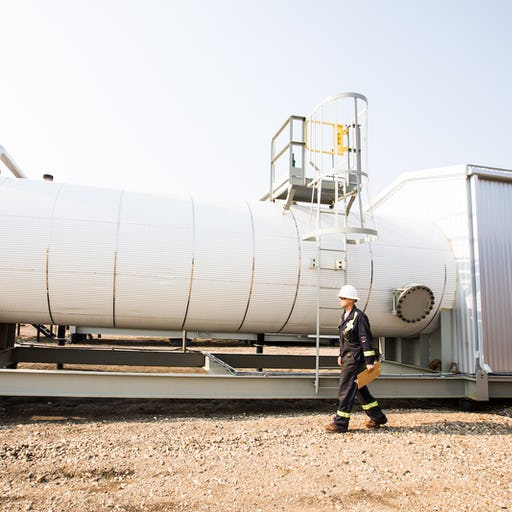 An oil worker walking with a clipboard, in front of a large white tank.