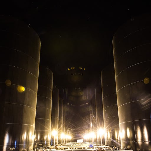 Oil drums at night, lit from the bottom by bright lights.
