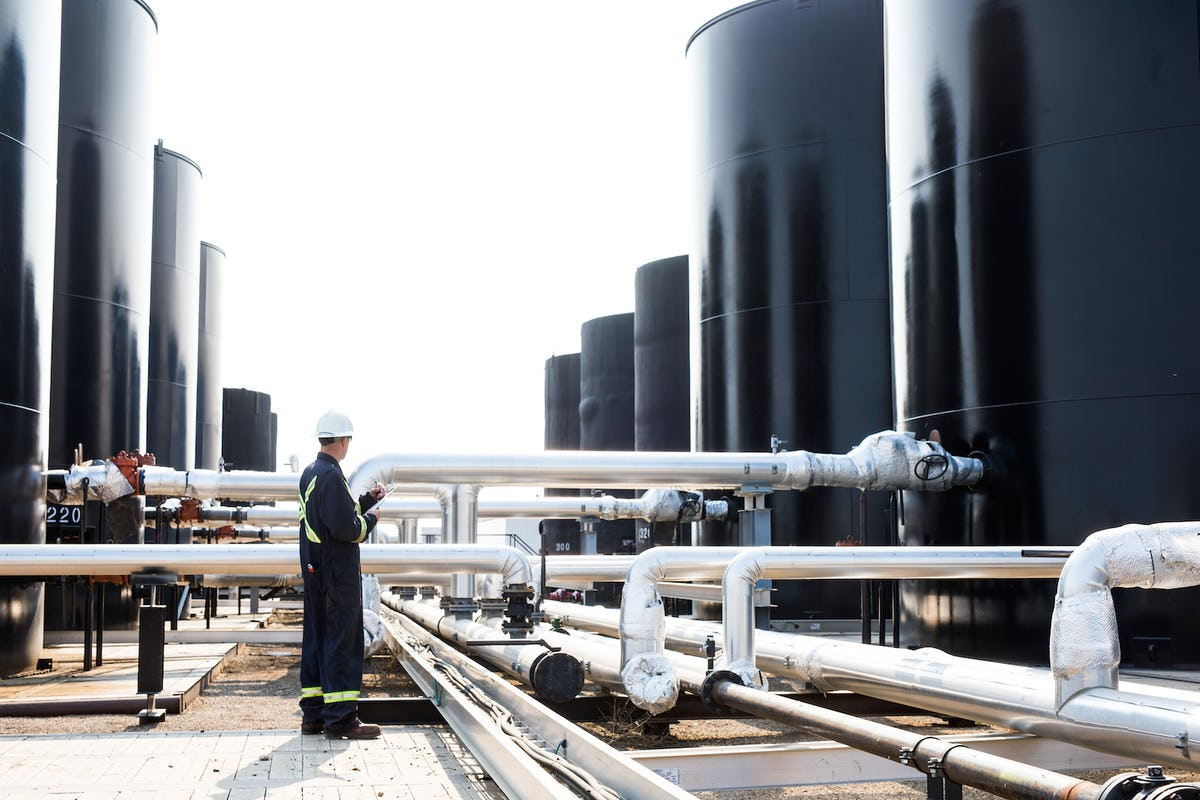 An oil worker monitoring large drums and pipes.