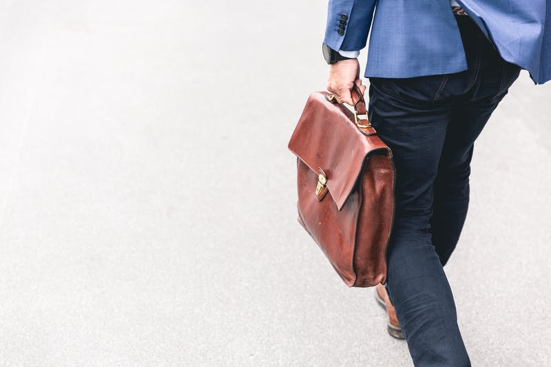 zzp'er in pak loopt met een tas over straat