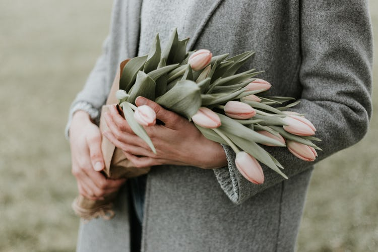 A white woman holding a bouquet of tulips on Mother's Day.