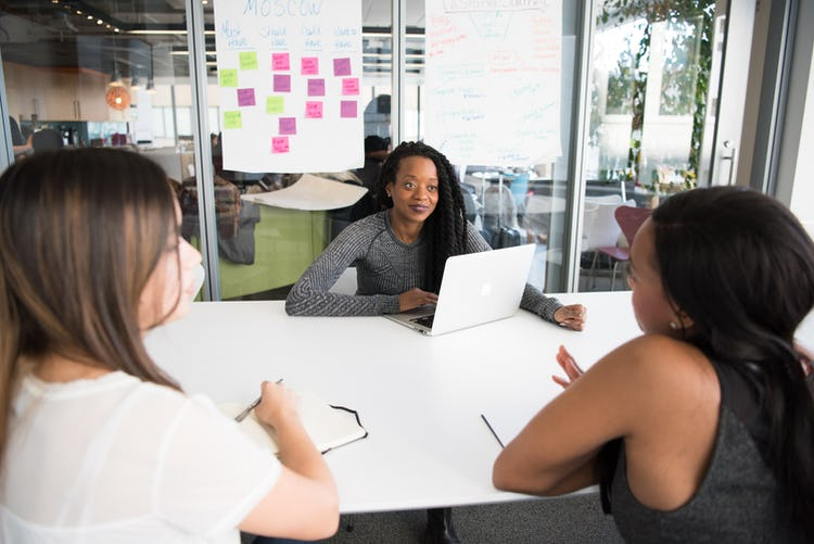 A young Black woman sitting in a meeting at work with other women.