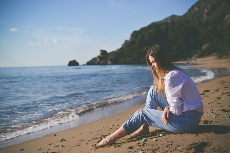 Depressed woman sitting on the beach because she is sad in the summer.
