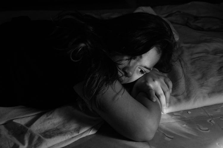 Black and white photo of woman with brown hair laying in bed using her arms as a pillow